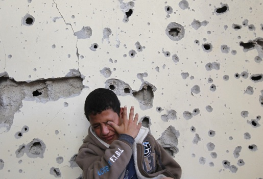 Palestinian boy Fares Sadallah, 11, cries as he sits outside his home which was damaged following an Israeli air strike in Beit Lahia, northern Gaza Strip, on November 16, 2012.