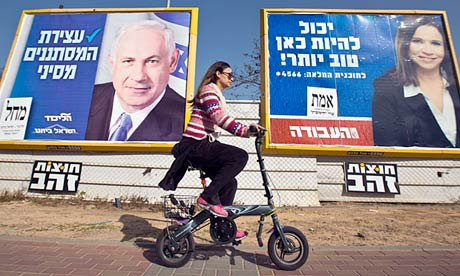 An Israeli woman rides her bicycle past election posters