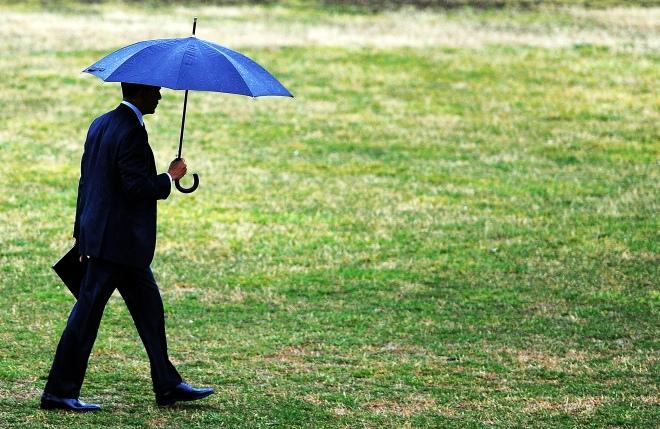 US President Barack Obama uses an umbrel