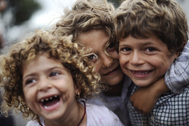 Roma children laugh in front of the came