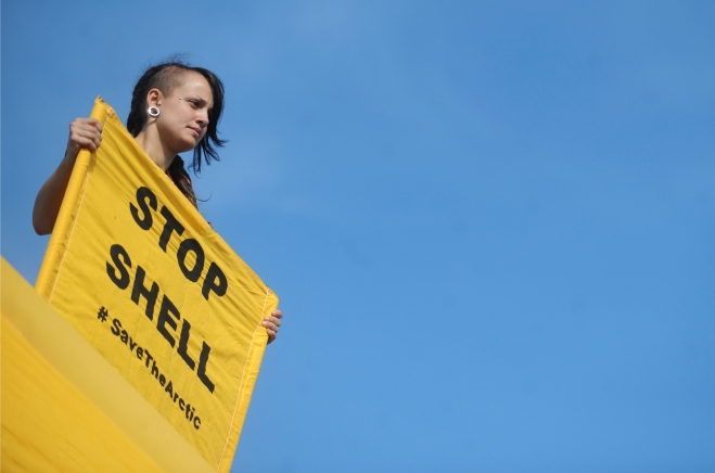 A Greenpeace activist holds a banner dur