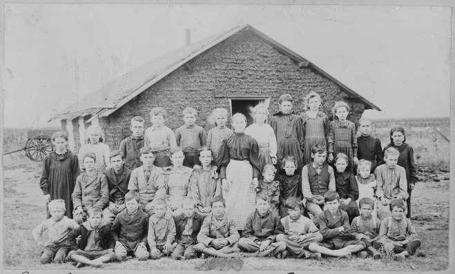 Teacher_and_children_in_front_of_sod_schoolhouse._Woods_Co.,_Okla._Terr.,_ca._1895_-_NARA_-_516448